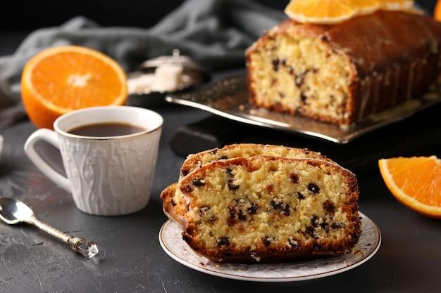Kleiner kuchen mit den orangen und schokolade gelegen auf einem behälter gegen einen dunklen hintergrund