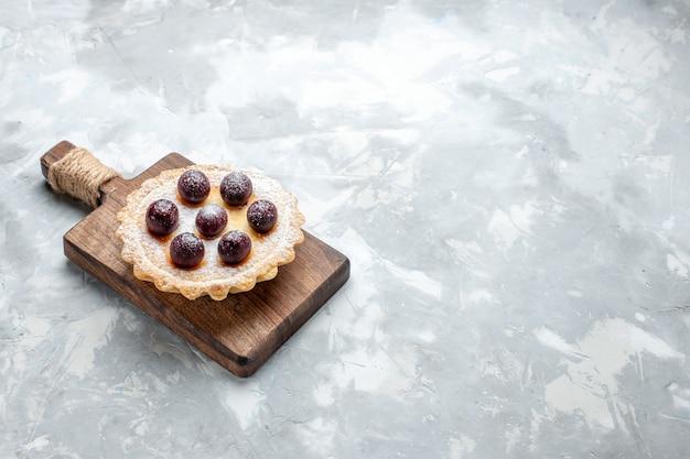 Kleiner kuchen mit früchten auf hellem schreibtisch, kuchenkeks süß backen