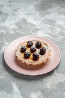 Kleiner kuchen mit früchten in rosa tellerlicht, tee süßer kuchen backen kuchen
