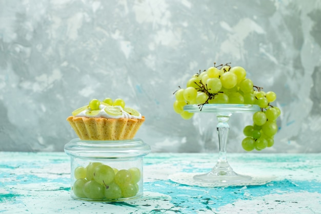 Kleiner kuchen mit köstlicher sahne und geschnittenen und frischen grünen trauben isoliert auf blauem kuchen süßer fruchtzuckerauflauf