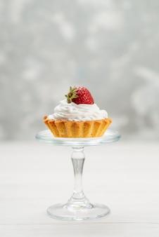 Kleiner kuchen mit sahne und erdbeere auf leichtem, frischem süßem kuchen der fruchtbeerenrot