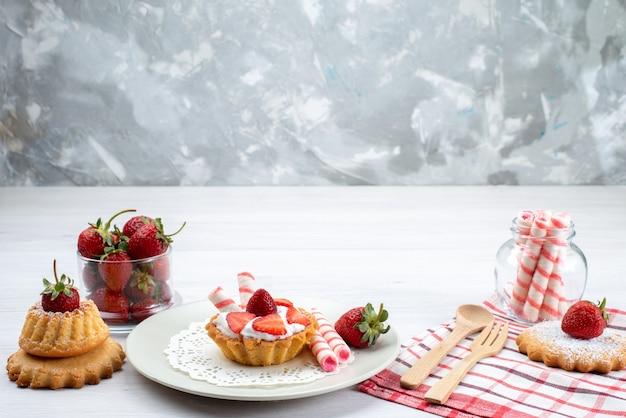 Kleiner kuchen mit sahne und geschnittenen erdbeerkuchen bonbons auf weißem schreibtisch, obstkuchen beerenzucker
