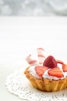 Kleiner kuchen mit sahne und geschnittenen erdbeersüßigkeiten auf weißem schreibtisch, obstkuchenbeere süßer zuckerauflauf