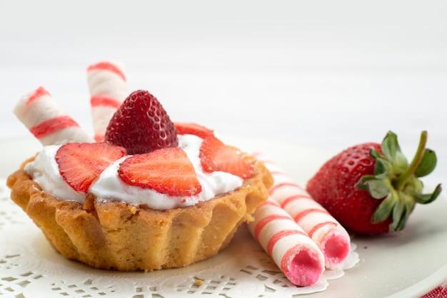 Kleiner kuchen mit sahne und geschnittenen erdbeersüßigkeiten auf weißem schreibtisch, obstkuchenbeerensüßzucker