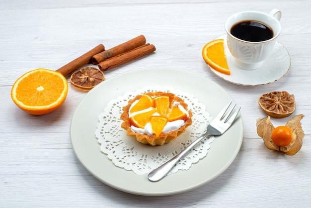 Kleiner kuchen mit sahne und geschnittenen orangen zusammen mit kaffee und zimt auf leichtem schreibtisch, obstkuchenkeks süßer zucker