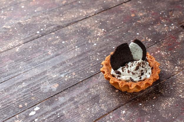 Kleiner kuchen mit sahne und schokoladenplätzchen lokalisiert auf hölzernem braunem schreibtisch, kuchenbiskuit-backfarbe