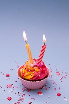 Kleiner kuchen mit sahne und zwei kerzen und ein pulver mit herzen auf einer blauen oberfläche. feiertagsbacken für valentinstag. das symbol zweier liebender