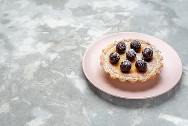 Kleiner kuchen mit zuckerpulver-fruchtcreme auf hellweißem, süßem kuchen-kuchenfrucht-tee