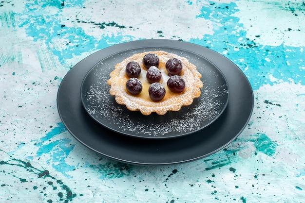 Kleiner kuchen mit zuckerpulver und früchten auf blauem, süßem tee mit kuchencremefrüchten