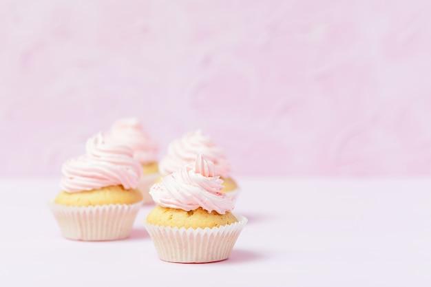 Kleiner kuchen verziert mit rosa buttercreme auf rosa pastellhintergrund. süßer schöner kuchen