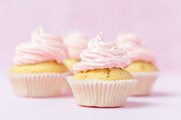 Kleiner kuchen verziert mit rosa buttercreme auf rosa pastellhintergrund.