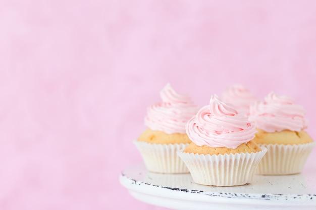 Kleiner kuchen verziert mit rosa buttercreme auf schäbigem shic stand auf pastellrosahintergrund.