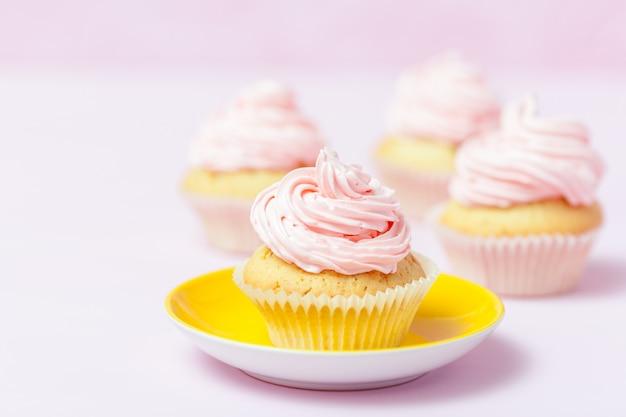 Kleiner kuchen verziert mit rosa buttercreme in der hellen gelben platte auf pastellrosahintergrund