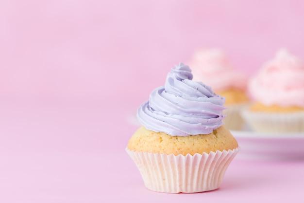 Kleiner kuchen verziert mit rosa und violetter buttercreme auf pastellrosahintergrund.