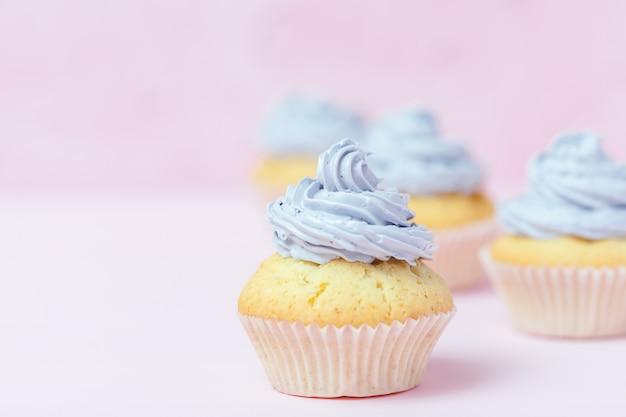 Kleiner kuchen verziert mit violetter buttercreme auf rosa pastellhintergrund.