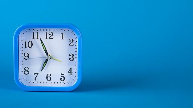 Kleiner kunststoff-wecker im retro-stil auf hellblauem hintergrund. banner.