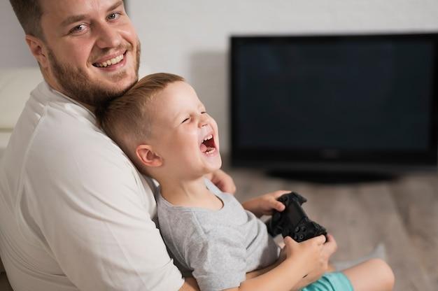 Kleiner lachender junge beim spielen mit prüfer