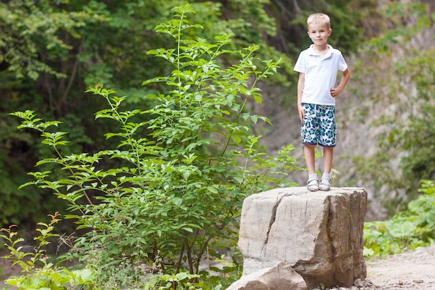 Kleiner lächelnder junge, der auf einem großen stein steht