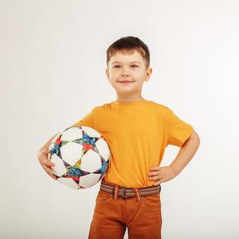 Kleiner lächelnder junge, der einen fußball unter seinem arm hält