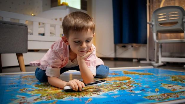 Kleiner lächelnder junge, der im schlafzimmer auf dem boden liegt und durch die lupe auf der großen weltkarte schaut. konzept von reisen, tourismus und kindererziehung. erkundungen und entdeckungen für kinder.