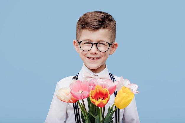 Kleiner lächelnder junge mit den gläsern, die blumen in seiner hand halten. , isoliert auf blauer wand