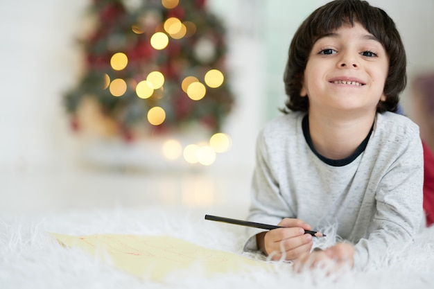Kleiner lateinamerikanischer junge, der in die kamera lächelt, während er bilder mit bunten bleistiften zeichnet und zu hause auf dem boden liegt, dekoriert für weihnachten. kind an kreativen aktivitäten beteiligt