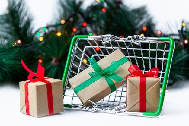 Kleiner lebensmittelkorb mit geschenkboxen auf weihnachtsbaumoberfläche mit girlandenlichtern