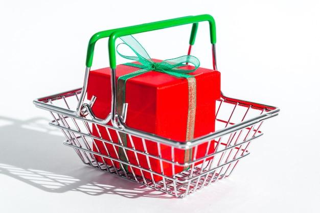 Kleiner lebensmittelkorb mit roter geschenkbox auf weißem isoliertem raum