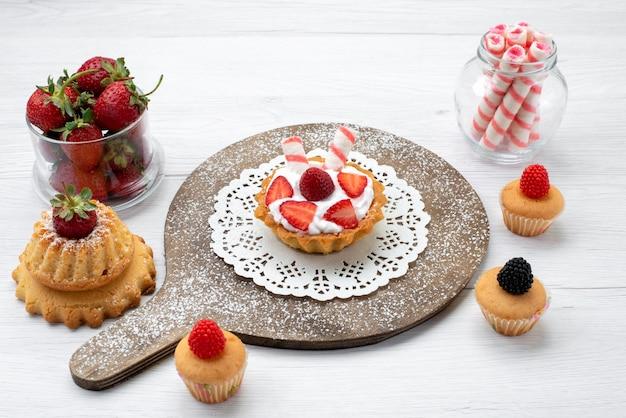 Kleiner leckerer kuchen mit sahne und geschnittenen erdbeerkuchen auf weißem boden kuchen beere süß backen obst backen