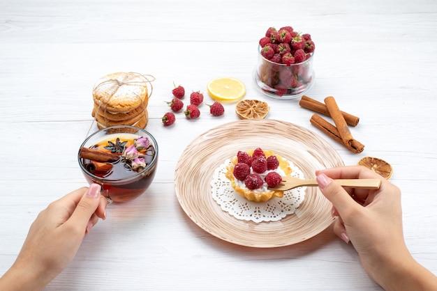 Kleiner leckerer kuchen mit sahne und himbeeren zusammen mit sandwichkeksen zimttee auf leichtem, fruchtigem beerenkuchen-keks süß