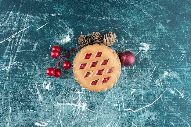 Kleiner leckerer obstkuchen mit weihnachtskugeln und tannenzapfen. foto in hoher qualität