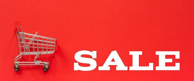Kleiner leerer einkaufswagenwagen und text verkauf auf rotem hintergrund.