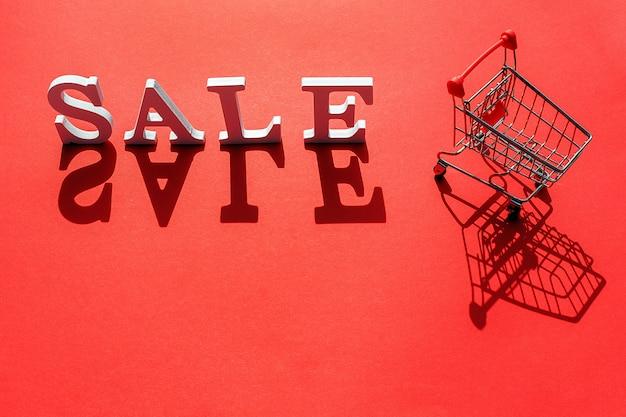 Kleiner leerer einkaufswagenwarenkorb und wort verkauf von weißen buchstaben wirft einen großen schatten auf rot