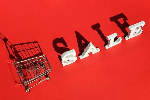 Kleiner leerer einkaufswagenwarenkorb und wort verkauf von weißen buchstaben wirft einen großen schatten auf rotem hintergrund