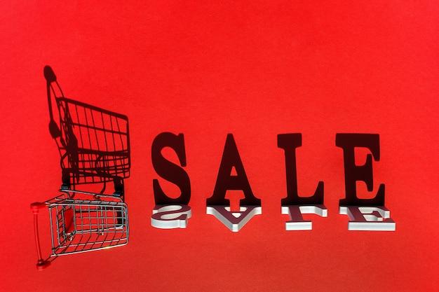 Kleiner leerer einkaufswagenwarenkorb und wort verkauf von weißen buchstaben wirft einen großen schatten