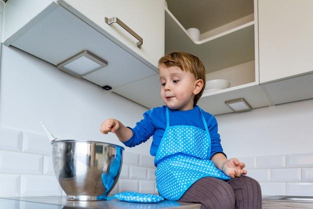 Kleiner lustiger entzückender kleiner junge, der küchenschürze trägt, die apfel-hauskuchen backt