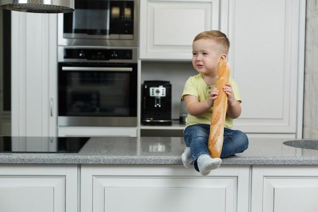 Kleiner lustiger junge, der ein brötchen in der küche isst. süßes baby isst baguette. porträt des attraktiven babys mit brot in den händen. junge beißt ein leckeres baguette .baby in bäckereien
