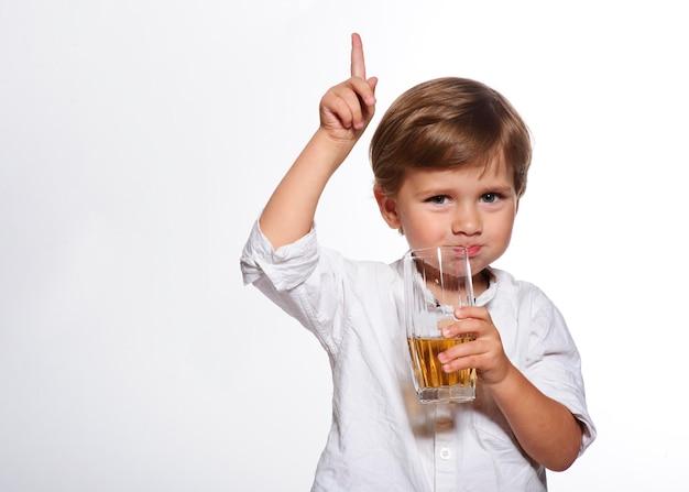 Kleiner lustiger junge, der einen frischen saft trinkt