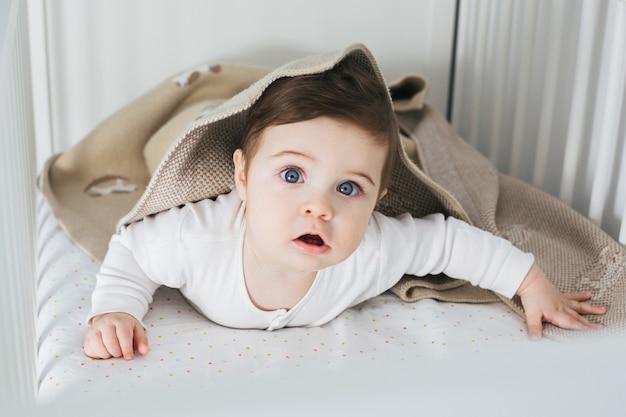 Kleiner lustiger junge, der im babybett liegt und lacht