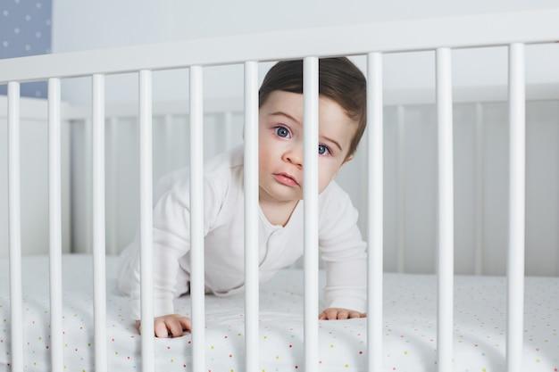 Kleiner lustiger junge, der im babybett liegt