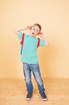 Kleiner lustiger junge, der mit gläsern, rucksack steht. überraschend. isoliert auf dem gelben.