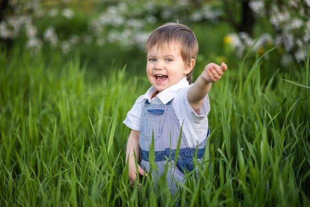 Kleiner lustiger junge in einem modischen blauen overall mit ausdrucksstarken blauen augen. süß lächelt und isst frisches grünes gras in einem großen blühenden garten im hohen gras.