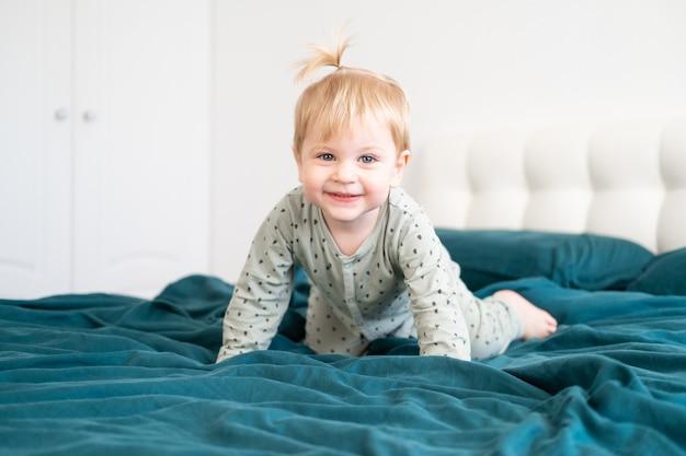 Kleiner lustiger kleinkindjunge im pyjama, der spaß im bett zu hause hat, grüne bettwäsche.