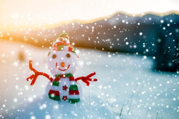 Kleiner lustiger spielzeugbaby-schneemann in der strickmütze und im schal im tiefschnee im freien auf verschwommener gebirgslandschaft und fallenden großen schneeflocken. frohes neues jahr und frohe weihnachten grußkartenthema.