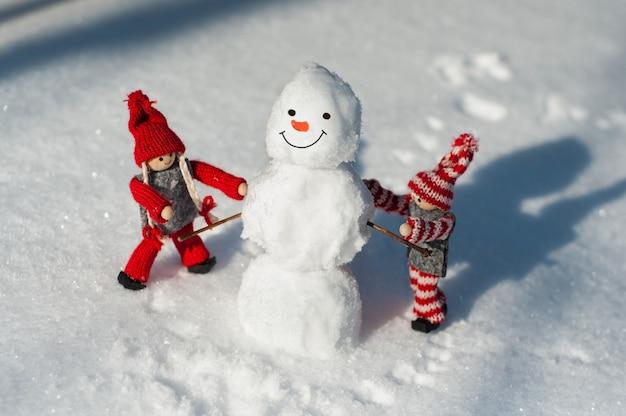 Kleiner mann mit zwei spielzeugen gemacht von einem schneemannschnee