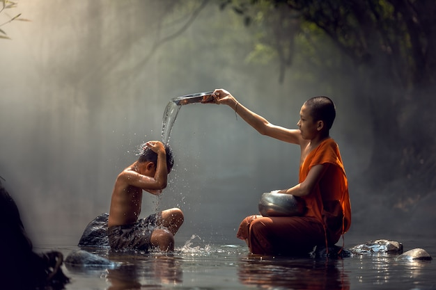 Kleiner mönch und kind, die ein bad am wasserfall, nong khai, thailand nimmt.