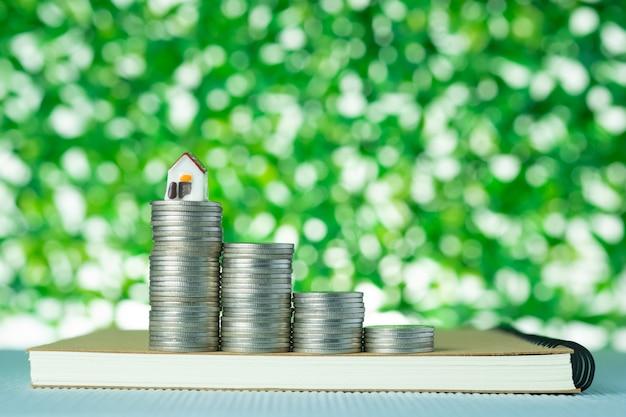 Kleiner musterhaus- und münzenstapel mit notizbuchgrünhintergrund