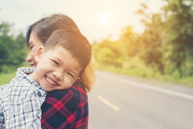 Kleiner netter asiatischer junge umarmung mit ihrer mutter und lächelnd zur kamera hap