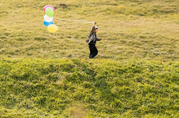 Kleiner netter junge auf graswiese mit ballonen