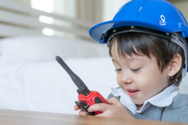 Kleiner netter junge, der blauen sturzhelm trägt und zur unterhaltung mit rotem funksprechgerät redio im schlafzimmer genießt